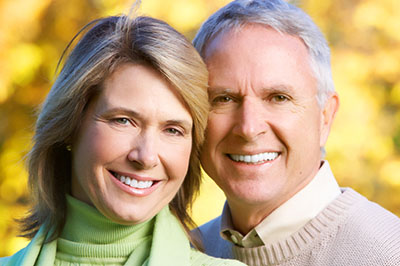 Eldery couple smiling in the yellow autumn background