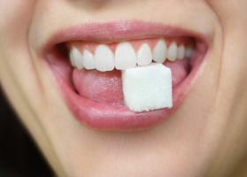 sugar cube in womans smiling mouth teeth